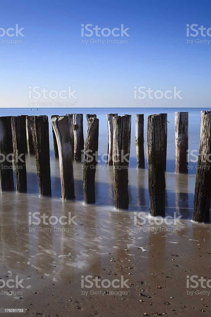 waves breaking on a wooden breakwater along the Dutch coast royalty-free stock photo