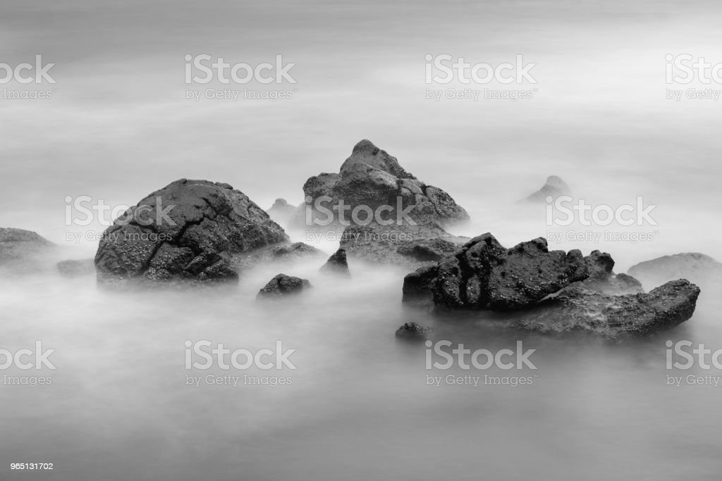 Waves breaking on large rocks in the Andaman sea. Views of the water and stones from Kata beach. Black and white landscape zbiór zdjęć royalty-free