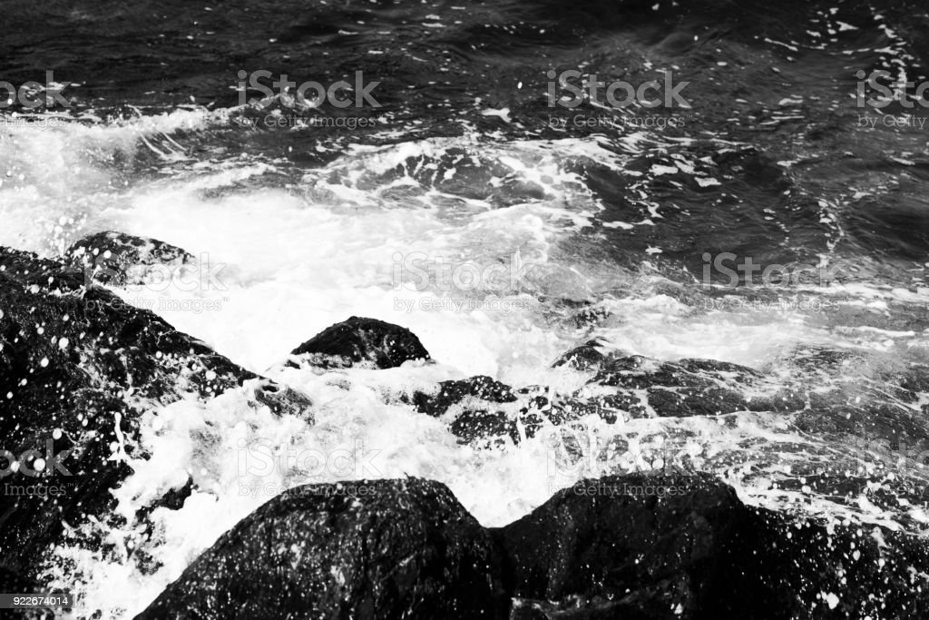 Waves breaking on rocky shore in black and white stock photo