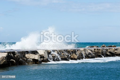 Waves hitting breakwater and breaking into a lots of drops during severe wind.