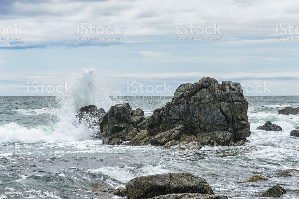 Waves breaking on the rocks . stock photo