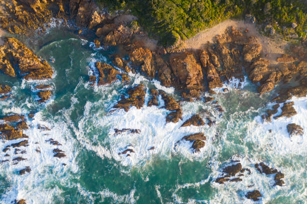 Waves breaking onto a rocky shoreline Aerial view of beautiful seascape. Waves are crashing on rocky coastline. Scenic view of ocean. rocky coastline stock pictures, royalty-free photos & images