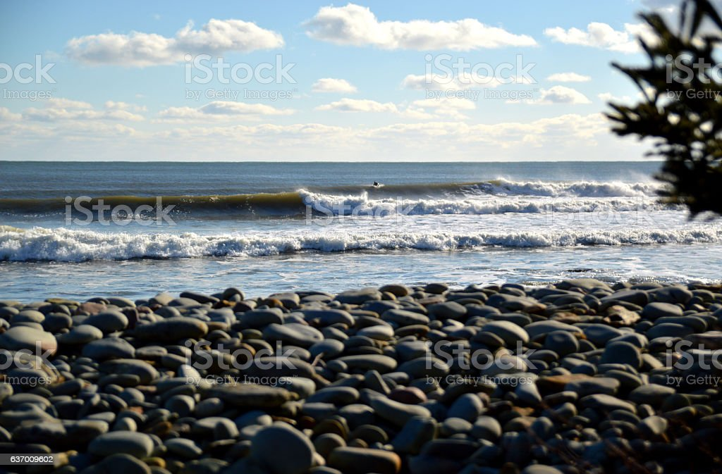 waves breaking right with surfer cobblestone foreground bohkeh stock photo