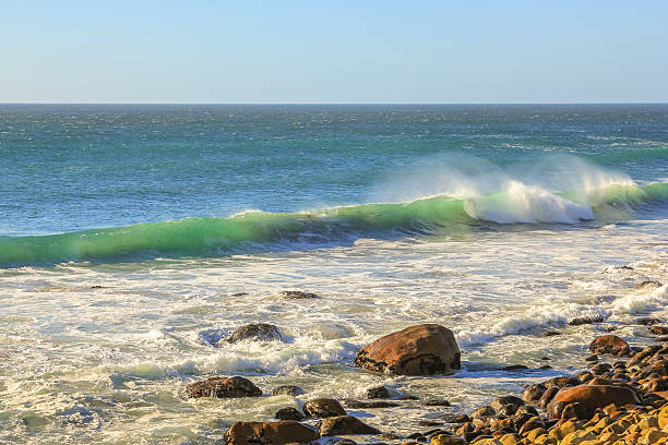 Waves Cape Town Turquoise waves breaking on rocks in Hout Bay, Cape Town, South Africa in the summer season. In winter Hout Bay is home to big waves for experienced surfers. hout stock pictures, royalty-free photos & images