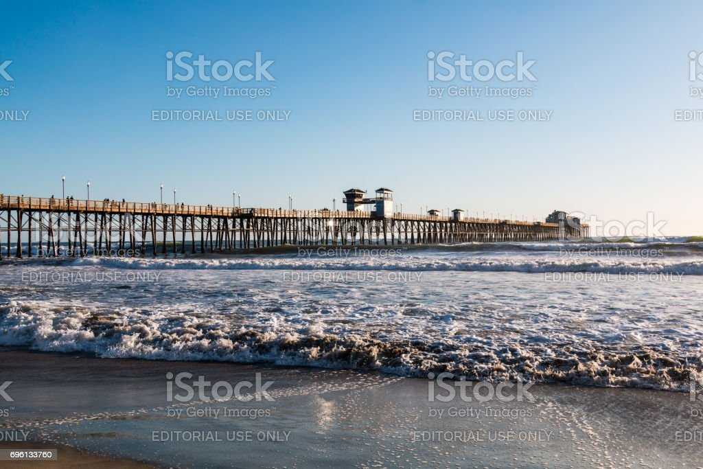 Waves Crash on Beach with Oceanside Fishing Pier stock photo