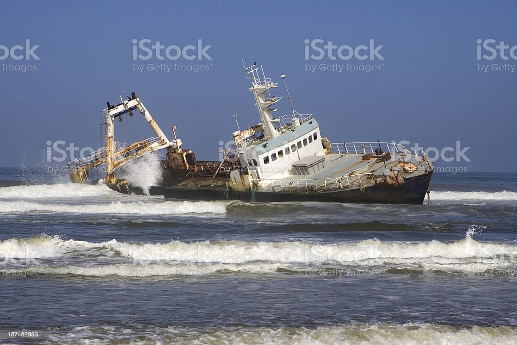Waves crash over fishing trawler shipwreck Skeleton Coast Namibia stock photo