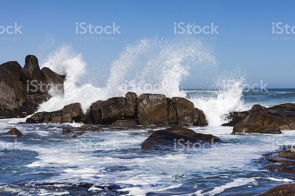 Waves crashing against boulders stock photo