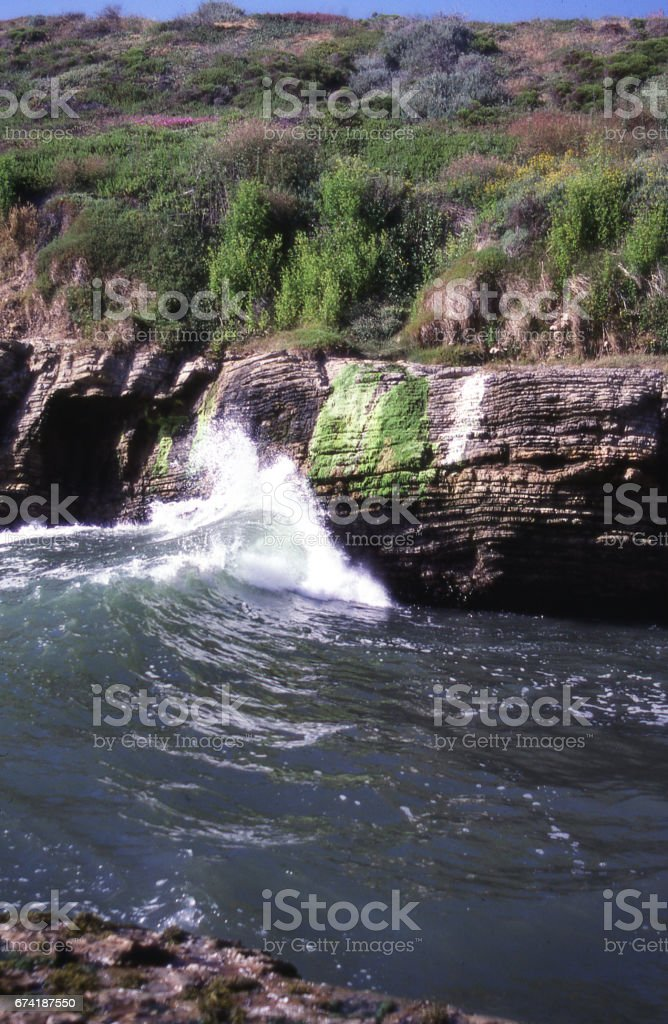 Waves crashing against cliffs at Montana de Oro State Park near Morro Bay California stock photo
