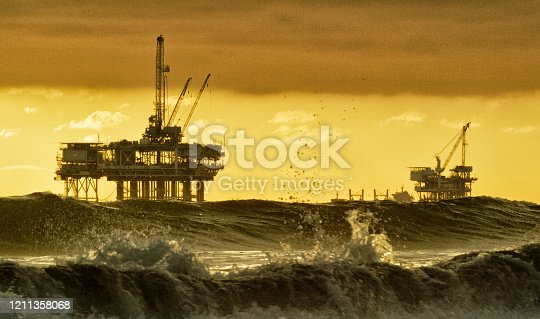 Waves Crashing and Splashing near Huntington Beach in Southern California with Several Silhouettes of Offshore Oil Drilling Rig Platforms and an Oil (Petroleum) Tanker on the Horizon in the Distance at Sunset under a Dramatic, Stormy Sky