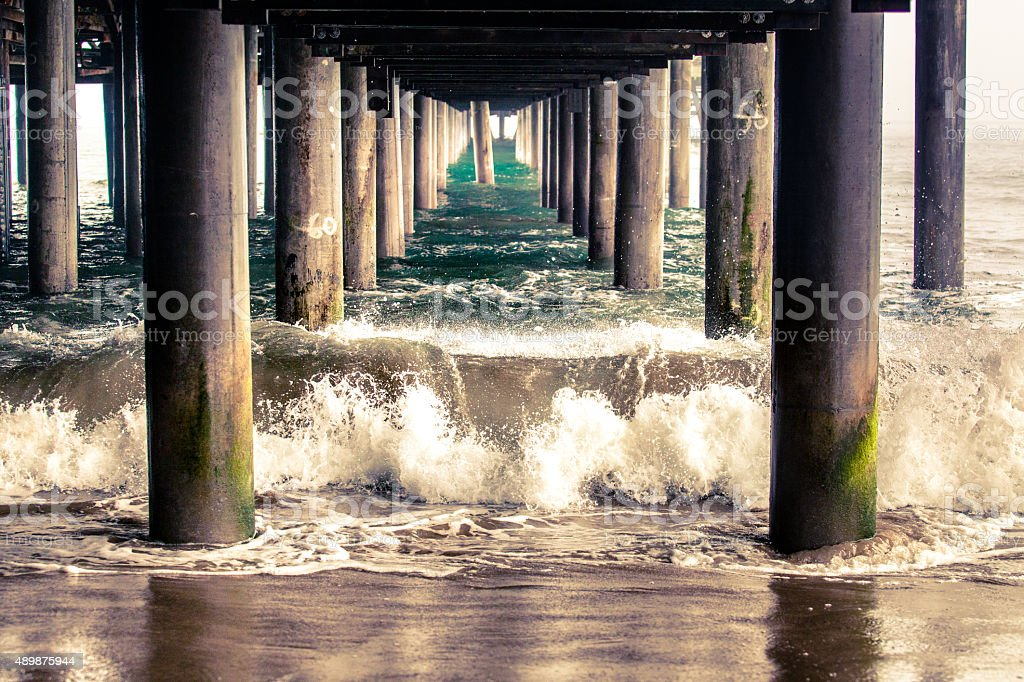Waves Crashing Between The Columns Underneath The Santa Monica Pier stock photo