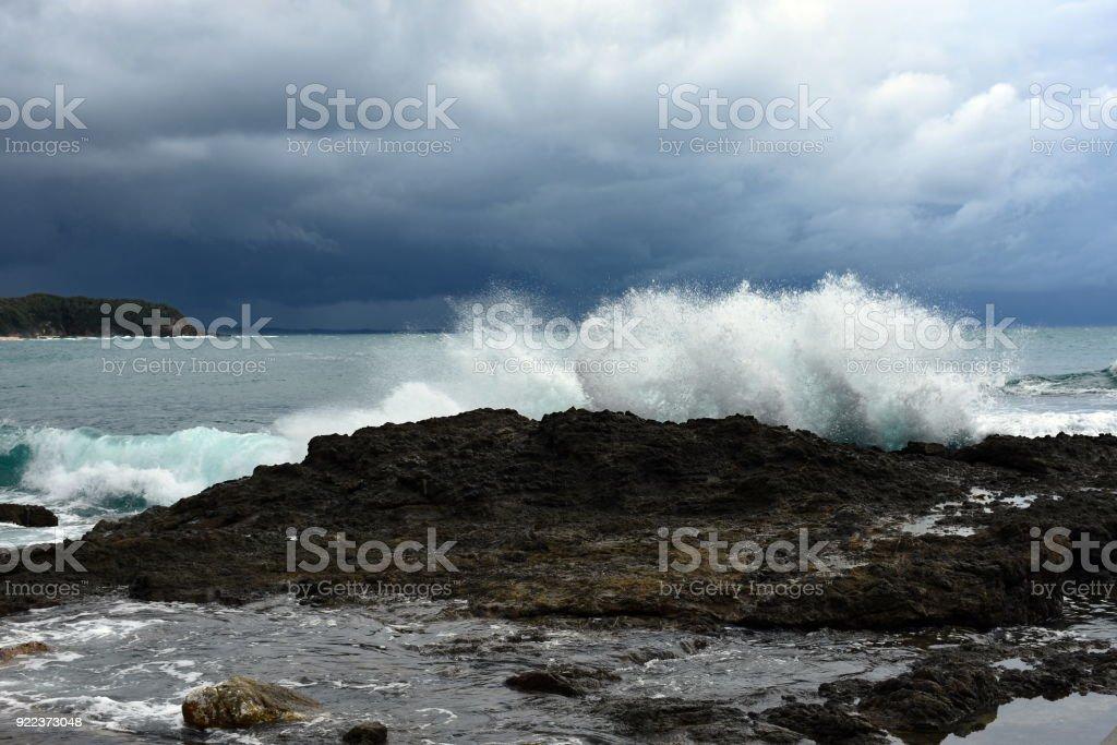Waves crashing into rocks stock photo