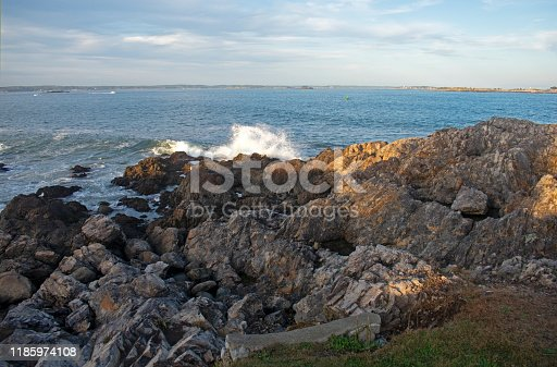 Small waves crashing into rocky shoreline viewed from Chandler Hovey Park in Marblehead, Massachusetts, USA.