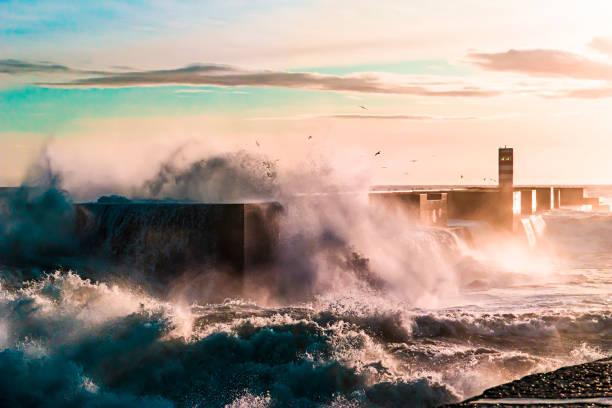 waves crashing on a pier at sunset - rain clouds porto portugal imagens e fotografias de stock