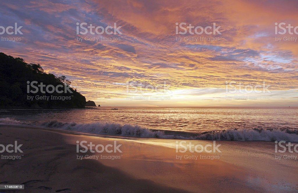 Waves Crashing on Beach at Sunset stock photo