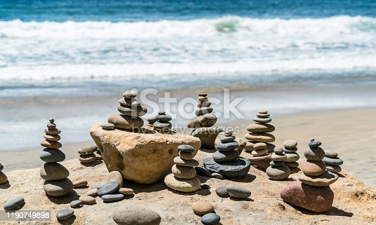 591835714 istock photo Waves crashing on the beach with tranquil rock piles 1190749898