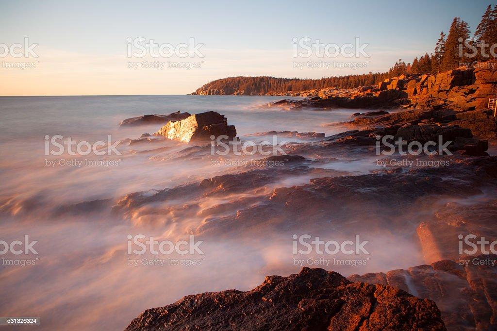 Waves crashing over rocks in Acadia National Park at sunrise. stock photo