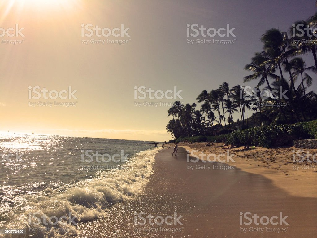 Waves ebb along a warm, sandy beach. stock photo