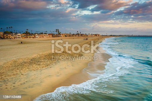 Waves in the Pacific Ocean and view of the beach at sunset in Seal Beach, California