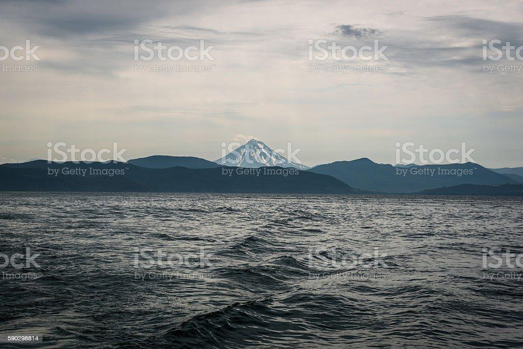 Waves leading the eye to Vilyuchinskaya Vulcano across Avacha Bay royaltyfri bildbanksbilder