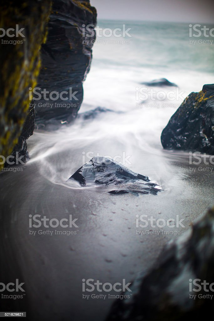 Waves move around a rock stuck in the sand stock photo