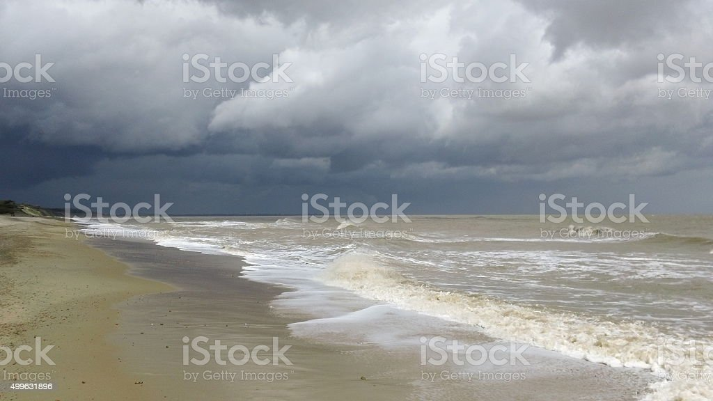 Waves on a deserted beach, stormy sky stock photo