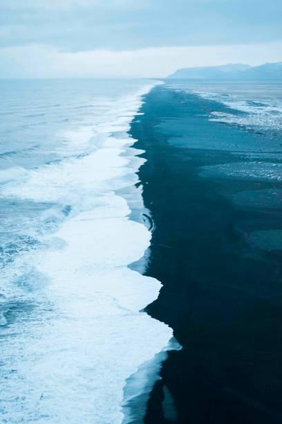 Wellen auf schwarzem Sandstrand – Foto