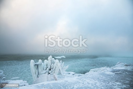 A view of the rough waters of Lake Huron from the Collingwood shoreline during  a winter storm with ice formations along the rocky shoreline.