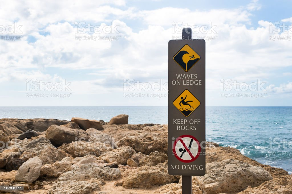 waves on ledge, keep off rocks, no diving sign stock photo