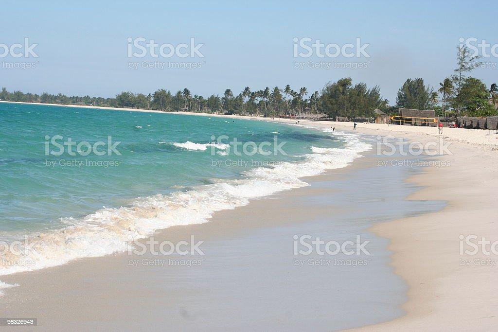 Onde sull'alberata sfondo con capanne di spiaggia foto stock royalty-free