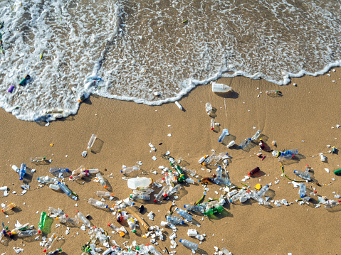 Plastic waste polluting the beach, mostly bottles that are pushed and attracted to the waves
