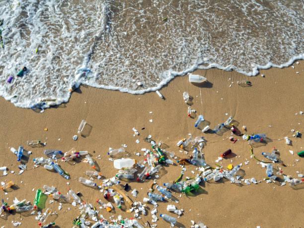 olas empujando residuos plásticos a la playa - contaminación ambiental fotografías e imágenes de stock