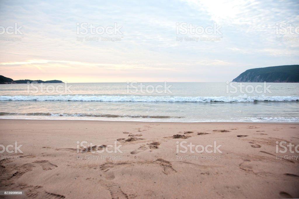 waves roll onto cape breton beach stock photo