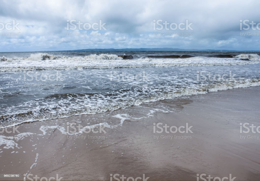 Waves rolling onto the beach with mountains on the horizon across the water and a stormy sky zbiór zdjęć royalty-free
