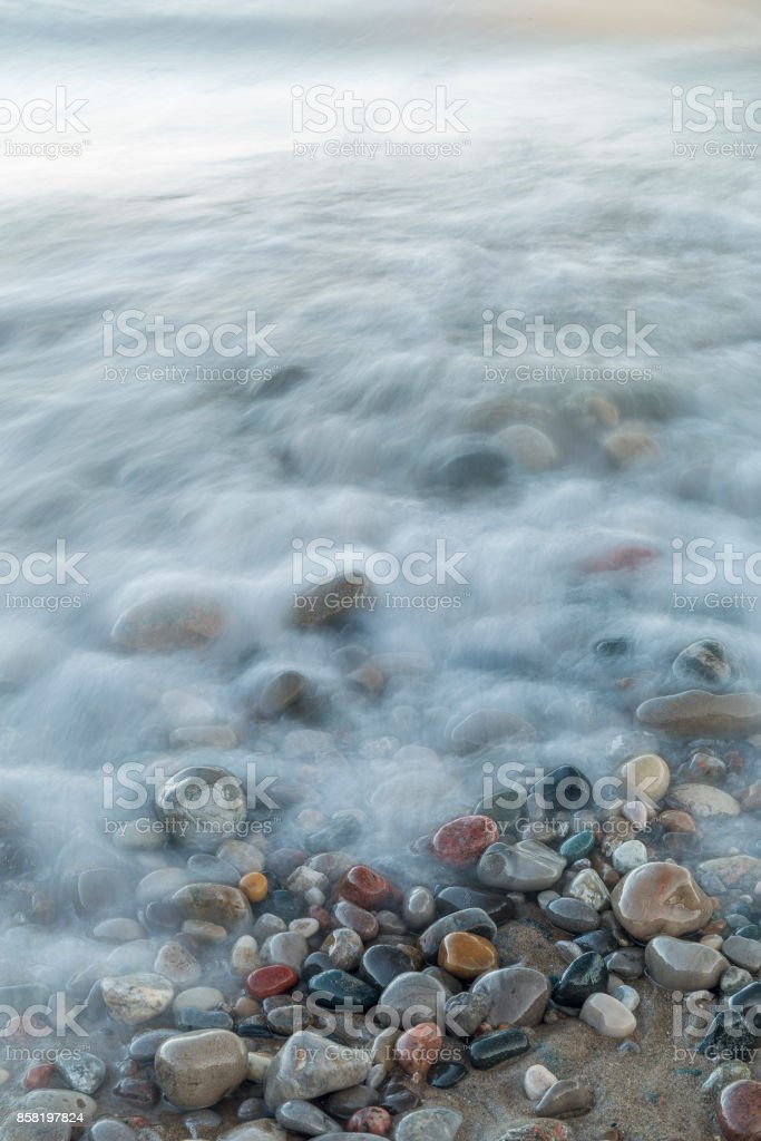 Waves rushing over stones on a Lake Huron beach stock photo
