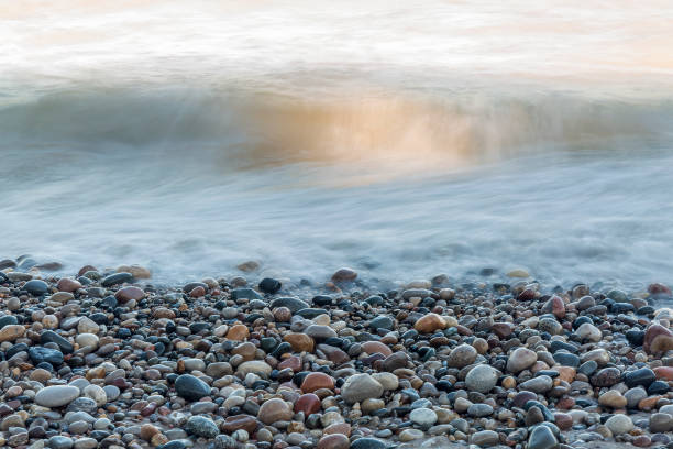 waves rushing over stones on a lake huron beach - lakeshore stock photos and pictures