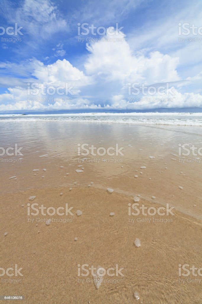 Waves sand beach and clouds sunny day stock photo