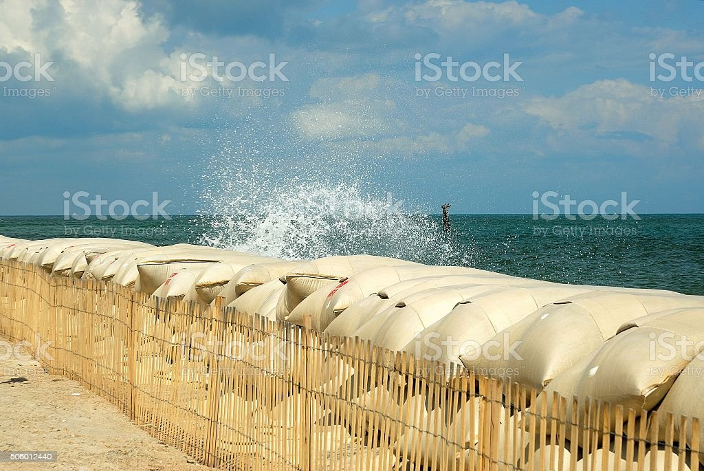 Waves spash against sandbags at northern end of the island stock photo