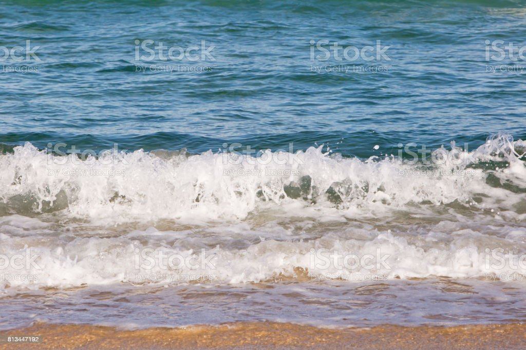 Waves spashing on to sand stock photo