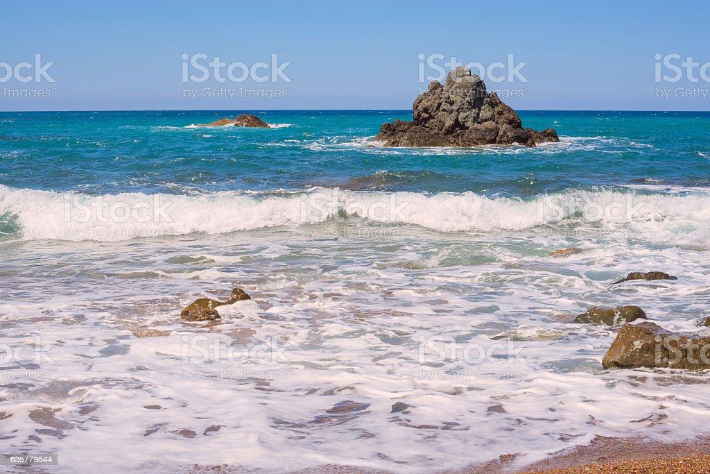 Waves splashes next to rocky coast stock photo