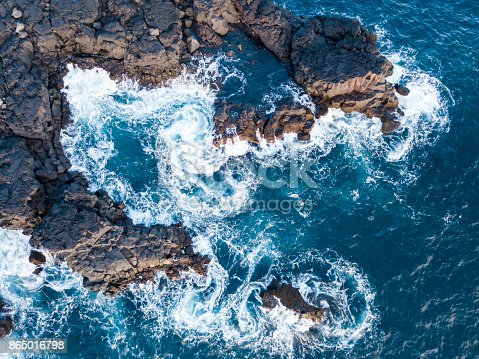Waves swirling and splashing against rocks from an aerial view.