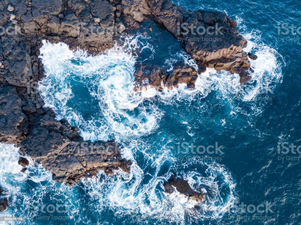 Waves splashing against volcanic rocks stock photo