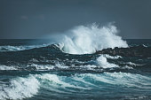 storm waves splashing at coastal rocks at la reunion island, mascarene islands, french overseas territory.