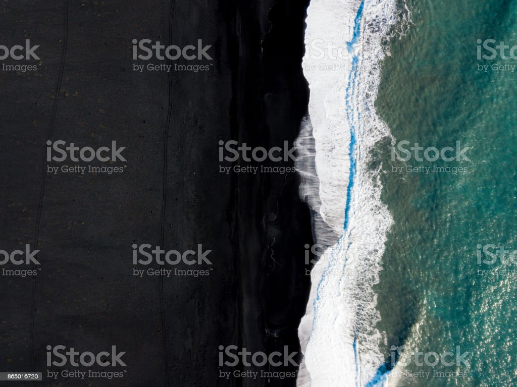 Waves splashing over a black beach stock photo