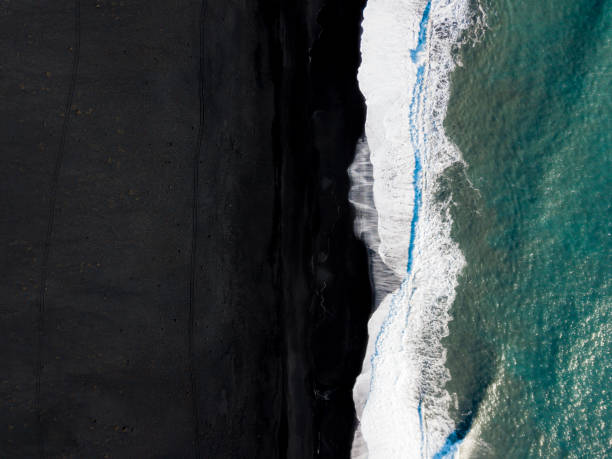 Waves splashing over a black beach Drone view of waves hitting black volcanic sand beach of Reynisfjara. black sand stock pictures, royalty-free photos & images
