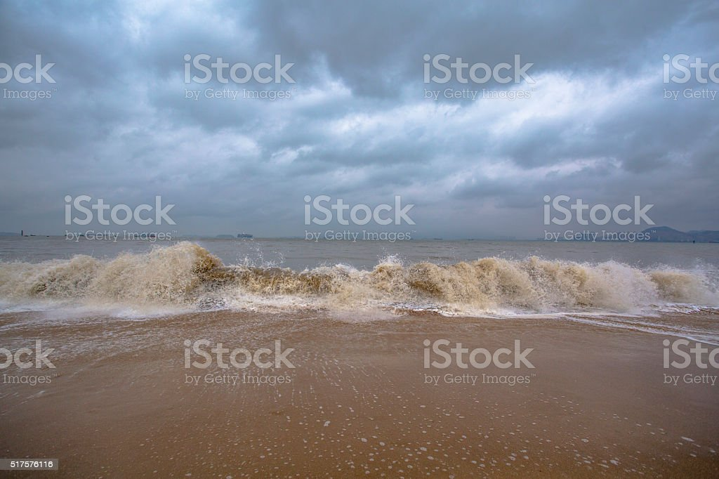 waves surfing on beach under overcast sky stock photo
