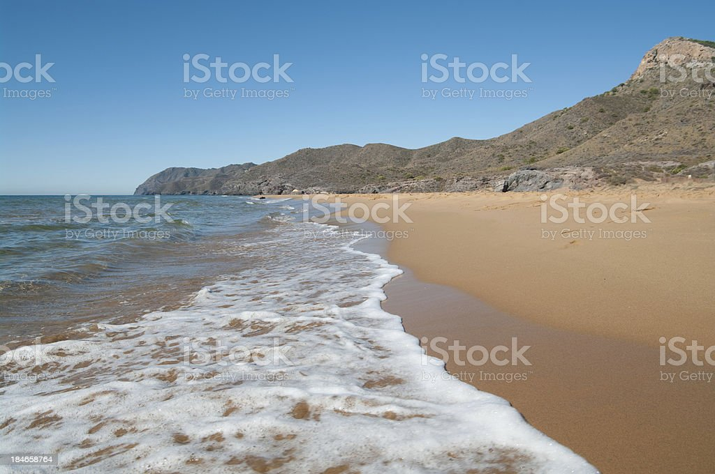 Waves wash ashore on remote beach in Spain stock photo