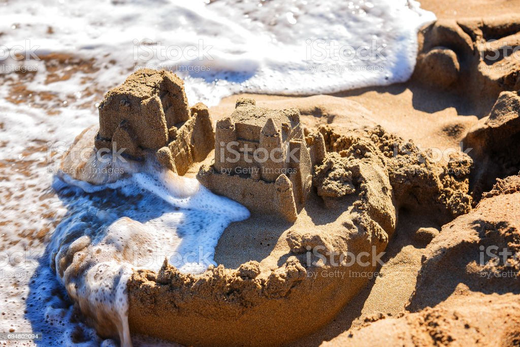 waves wash away sand castles on beach the sea stock photo