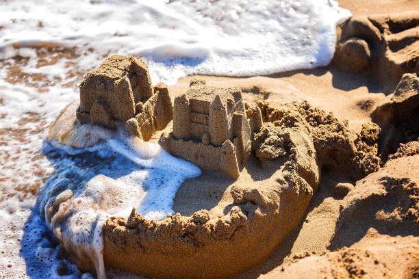 vagues de laver des châteaux de sable sur la plage de la mer - chateau de sable photos et images de collection