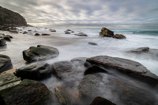Waves_flowing_over_rocks_beach_clouds 1 stock photo