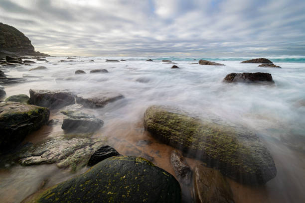 Waves_flowing_over_rocks_beach_clouds 2 stock photo